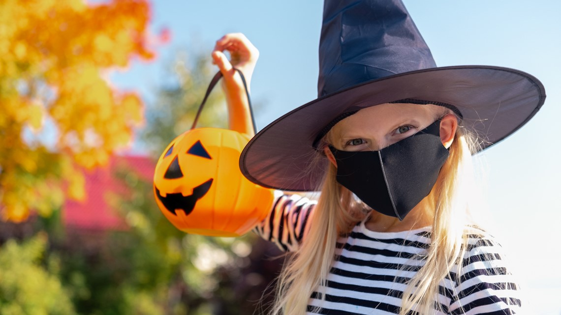 Young girl with plastic pumpkin in hand with mask.