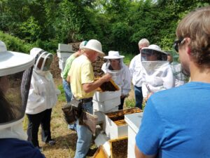 people in beekeeping suits with bee boxes